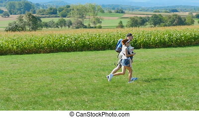 Family running on the field - Young couple with an...