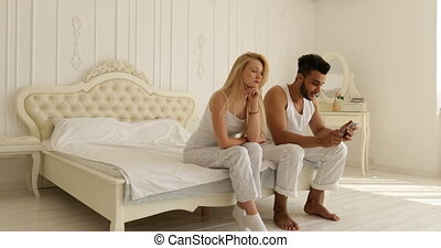 young couple relationships problem conflict sitting on bed...