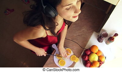 Dance with a knife in the kitchen - A girl listens to music...