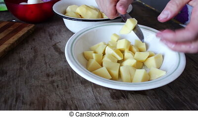 Chef cutting Potato with knife - Female hands cut diced raw...