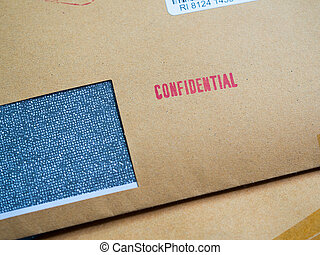 "Red ""Confidential"" word printed on brown vintage envelope in macro. Business confidential concept."