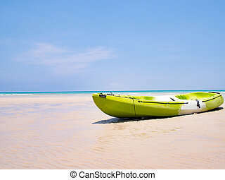 Green Kayak boat on the tropical beach background and clear blue sky at sea. Happy summer holiday concept