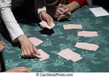 Female croupier shuffling cards on gambling table - Croupier...