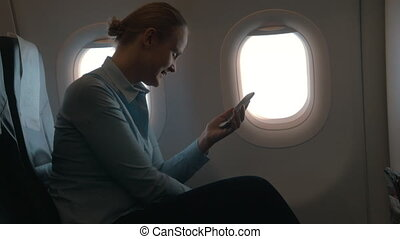 In cabin of plane girl sitting on chair and using mobile terminal on phone and pays for purchase through card