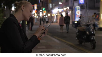 Woman working with pad in night Seoul street, South Korea -...
