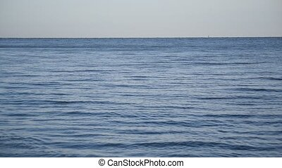 Blue sea or ocean with smooth water surface and ripples and...