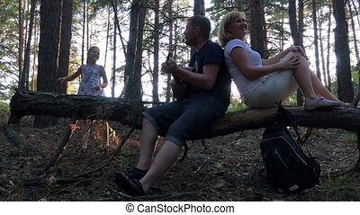 The family in the woods playing guitar