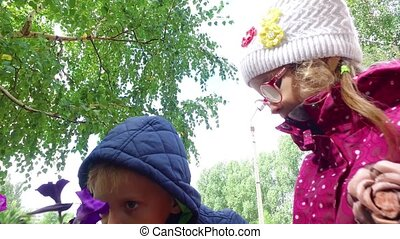 Blond boy and girl with glasses sniffing flowers. Children...