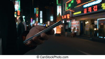 Woman browsing online on cell in night Seoul, South Korea -...
