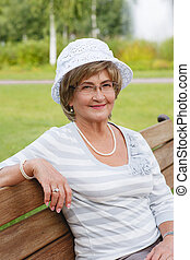 Happy senior woman sitting on a bench