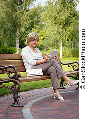 Attractive mature woman using digital tablet in a park -...
