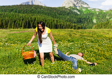 Woman pulling a slapped man after summer picnic in near the...
