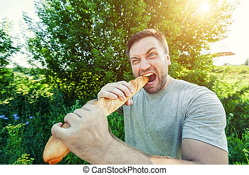 Man eating French bread - Bearded man nibbling French bread...