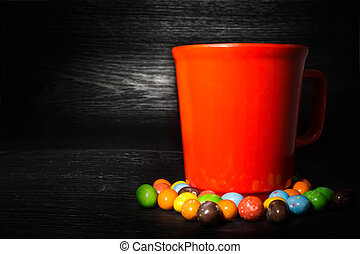 Colorful candy surround of red cup on black wooden texture...
