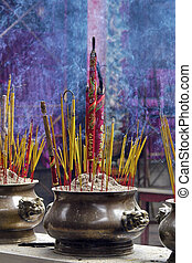 Incense offerings at the temple - Blue smoking incense at...
