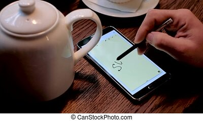 Man writes SOS inscription on the smart phone screen using...