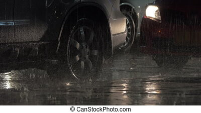 Parked cars under the rain at night - Two cars parked at the...