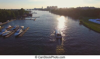 Sunset aerial follows riverboat. Boat floating along the...