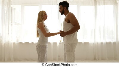 Couple love embrace walking to window open curtains mix race man woman rear view hug morning bedroom