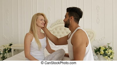 Couple love embrace smile sitting bed face to face mix race...