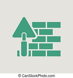 Icon of brick wall with trowel. Gray background with green....