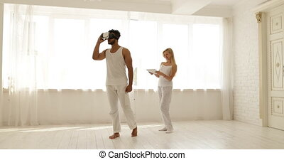 Man using virtual reality glasses woman holding digital...