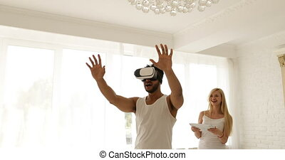 Man using virtual reality glasses woman holding digital tablet