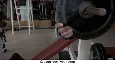 Young man at the gym doing exercise chest press with rod -...