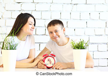 Young smiling couple sitting at the table