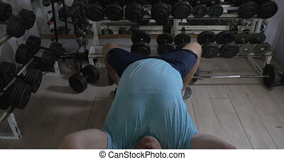 Grown man in a gym lying on bench and raises damn over head...