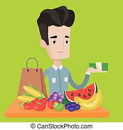 Young man standing at the table with shopping bag, fruits...