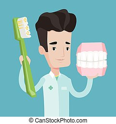 Dentist with dental jaw model and toothbrush. - Young...