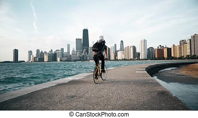 Cyclist rides at seaside with skyscrapers on the background
