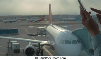 Paying online with mobile card reader - Woman at the airport...