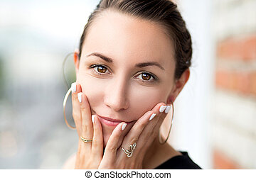 Portrait of young girl with hands in face