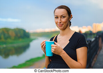 Girl stands outside with blue cup
