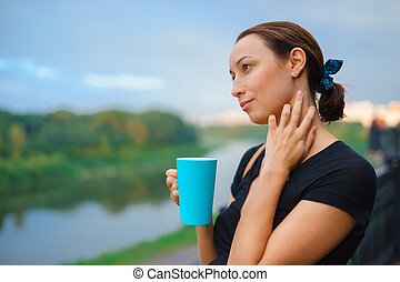 A girl stands outside with cup of tea