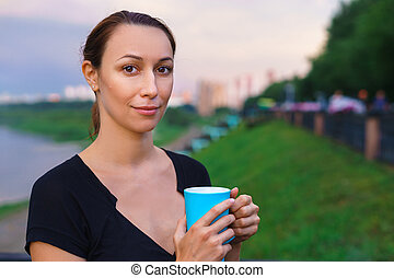 A girl stands with cup of tea