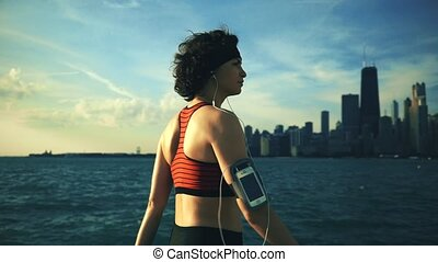 Runner athlete walking at seaside with skyscrapers on the background