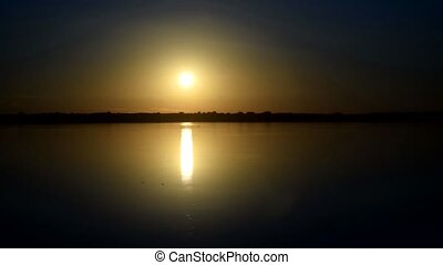 Dramatic sunrise over calm smooth water surface of river