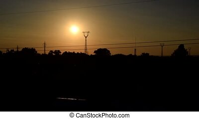 Landscape with sun rusing behind transmission towers - Urban...