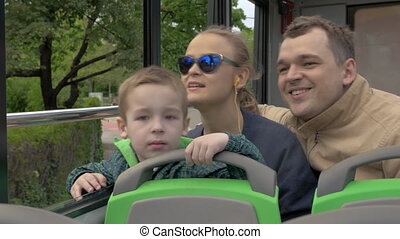 Family of three riding in doubledeck bus - Mother, father...