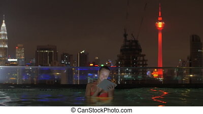 View of woman in swimming pool on the skyscraper roof using tablet against night city landscape.