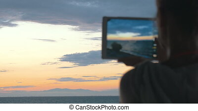 Woman takes photos of the beautiful scenery of the sea and evening sky with her tablet at sunset