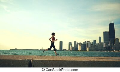 Runner athlete running at seaside with skyscrapers on the background