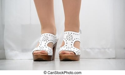 Female feet shod in white leather clogs - Female feet shod...