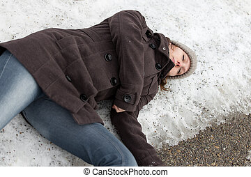 young woman lying unconsciously on a icy street, accident because of black ice