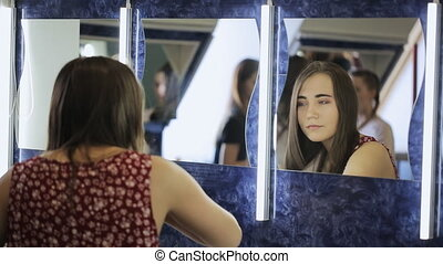 Young female is straightening hair in model school. Woman is...