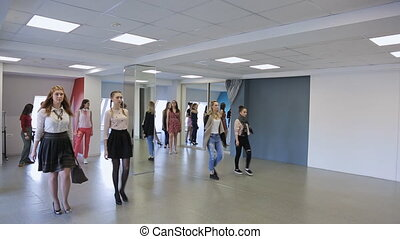 Handsome females train in catwalk in spacious ballroom.