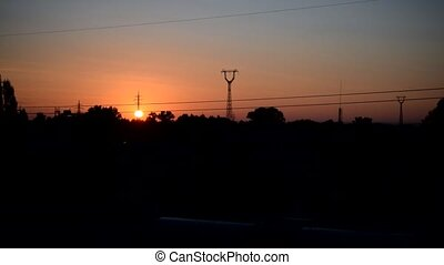 Cityscape with sun rusing behind transmission towers - Urban...
